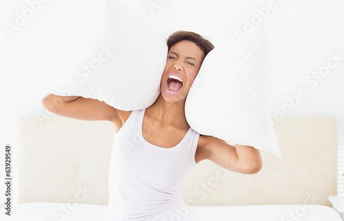 Screaming brunette sitting on bed covering ears with pillow