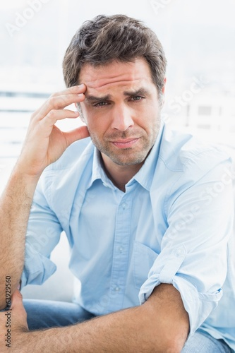 Wincing man with headache sitting on the couch looking at camera
