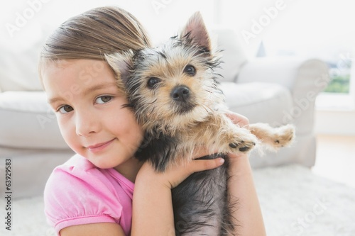 Smiling little girl holding her yorkshire terrier puppy