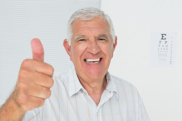 Smiling senior man gesturing thumbs up with eye chart in backgro