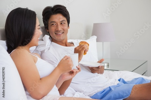 Happy couple having breakfast in bed