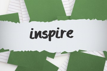 Inspire against green paper strewn over notepad