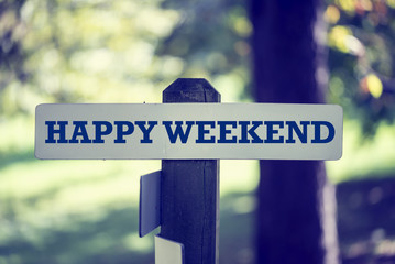 Old rustic signpost with the words, Happy Weekend