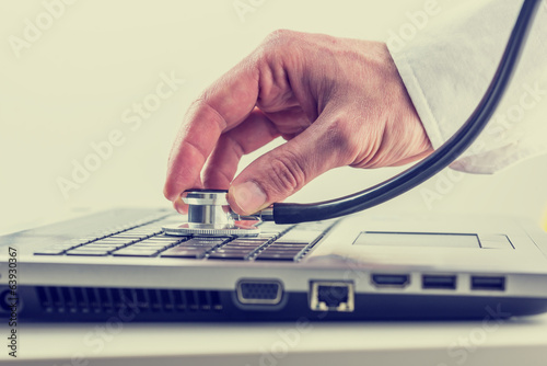 Man checking his laptop with a stethoscope