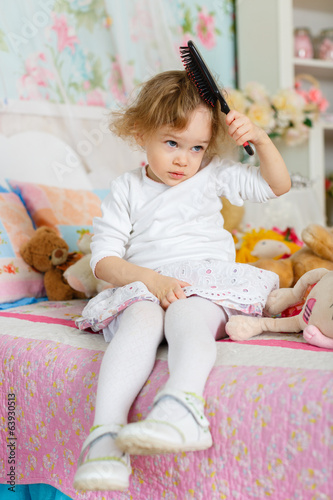 Little girl with hairbrush.
