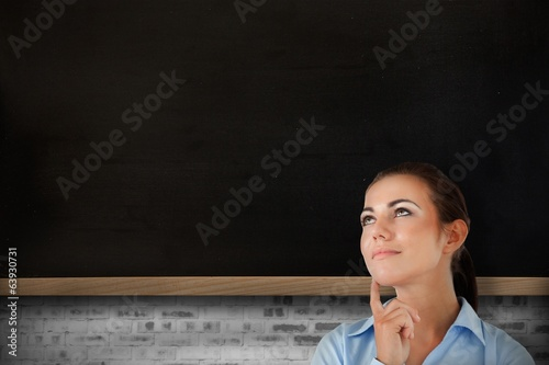 Composite image of thinking businesswoman looking upwards