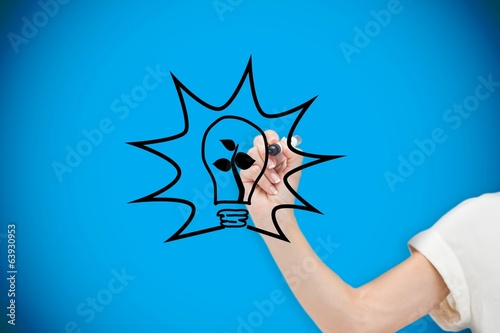 Composite image of businesswoman drawing light bulb