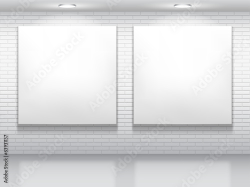 Two blank white pictures on brick wall.
