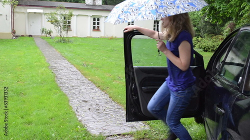 Girl with umbrella get out from car and walk cobble path in rain