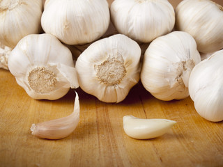 Organic garlic whole and cloves on wood