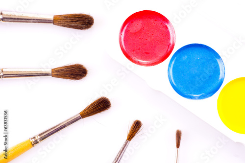 Set of watercolour paints and paintbrushes on white