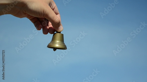 Male and female hands ding with silver bronze bell on blue sky