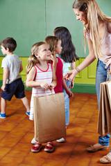 Erzieher verteilt Geschenk an Kinder