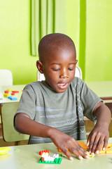 Afrikanisches Kind spielt im Kindergarten