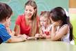 Leinwanddruck Bild - Kinder lesen Buch mit Erzieher in Kindergarten