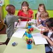 Kinder malen mit Erzieherin im Kindergarten