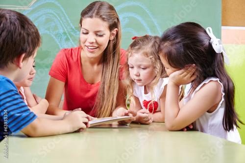 Leinwanddruck Bild Kinder lesen Buch mit Erzieher in Kindergarten