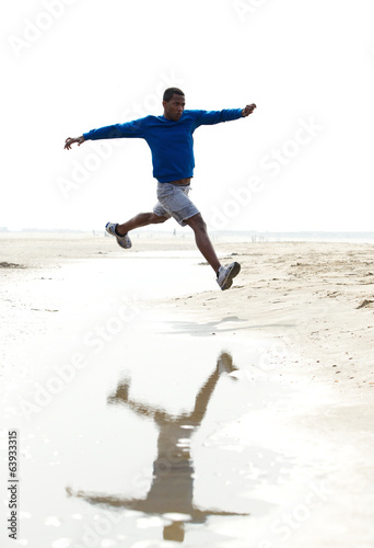 Young athletic male running at the beach