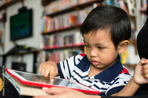 asian child playing with tablet