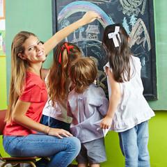 Erzieher und Kinder beim Malen an Tafel