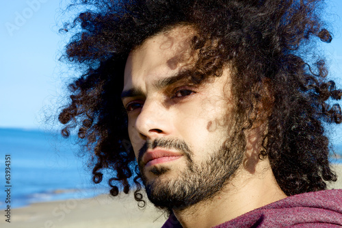 Closeup of serious young man looking the sea