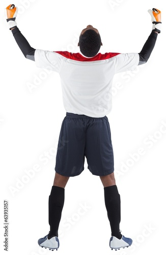Excited goalkeeper in white cheering