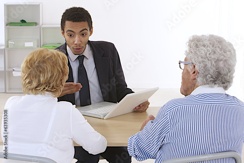 Elderly couple listening to sale speech of a financial adviser