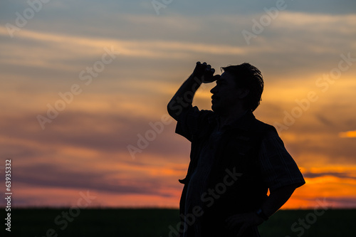 silhouette of man standing in a field