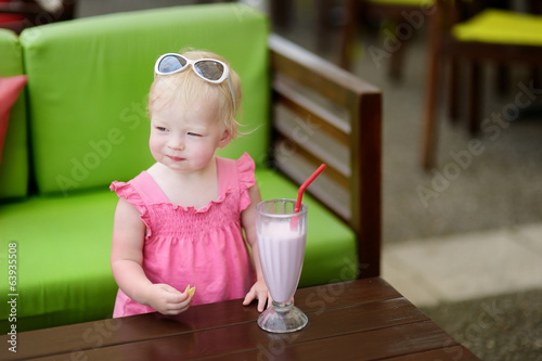 Little girl drinking milkshake in a restaurant