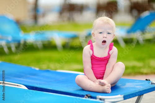 Toddler girl sitting on a sunbed by a pool
