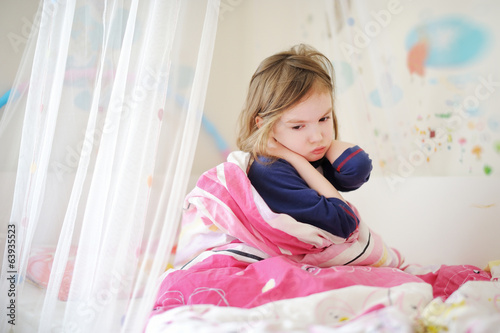 Little preschooler girl in pajamas on morning