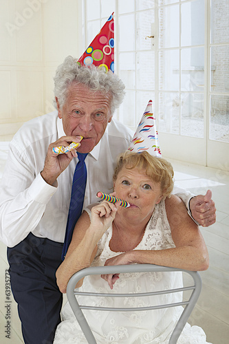 funny elderly couple in festivity blowing