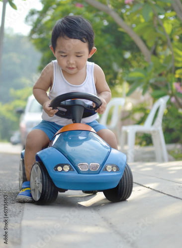 Asian baby boy rides his toy card