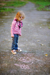 Little girl looking at a chalk drawing