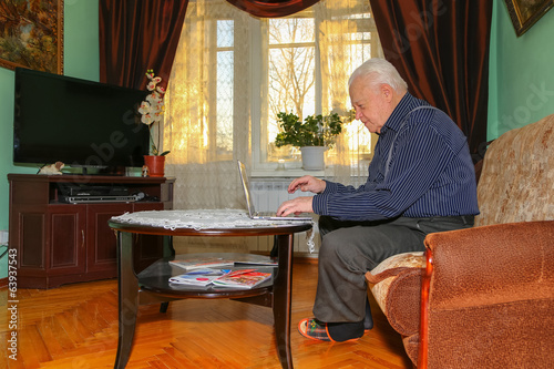 Old man with notebook at home