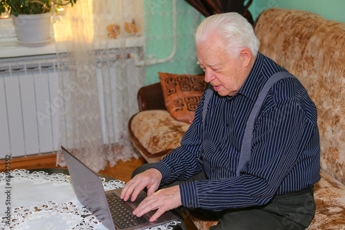 Grandfather with notebook at home