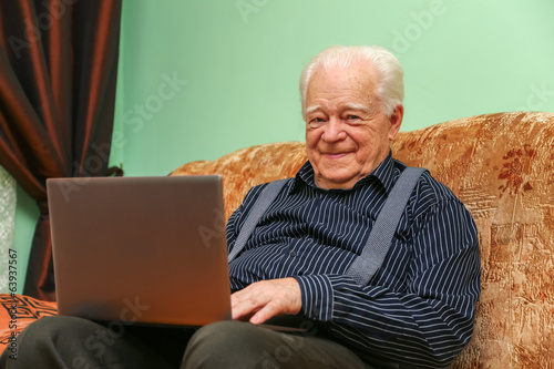 Aged man with notebook on the sofa