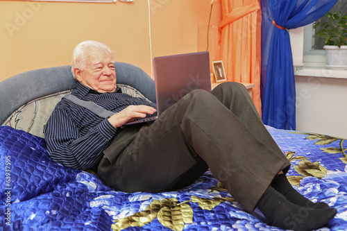 Aged man with notebook on the bed