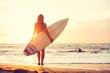 Leinwanddruck Bild - Surfer girl on the beach at sunset
