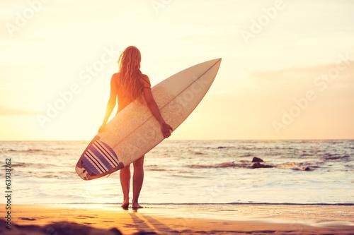 Leinwanddruck Bild Surfer girl on the beach at sunset