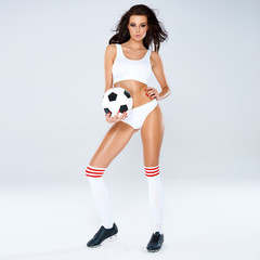 Sexy beautiful woman posing with a soccer ball