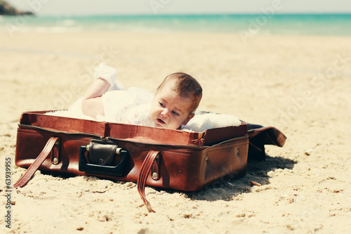 cute 2-month old baby lying in vintage case on the beach