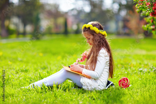 cute girl reading book, sitting on spring lawn