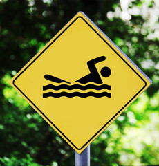 Yellow traffic label with swimming pictogram