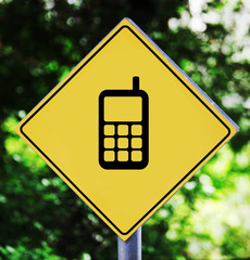 Yellow traffic label with cellphone pictogram
