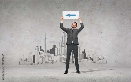smiling businessman with arrow on white board