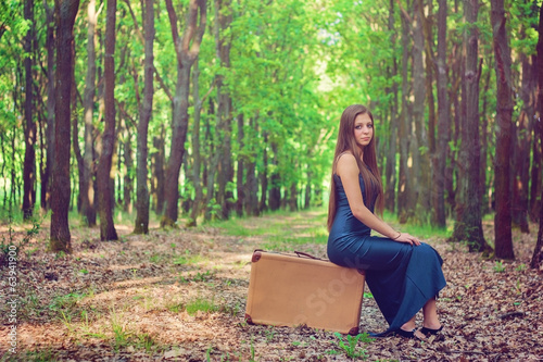 Girl sitting on an old luggage