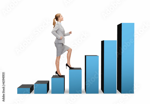 smiling businesswoman stepping on chart bar