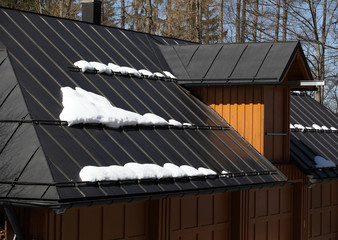 Metal roof of house with snow