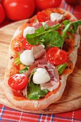 Homemade pizza with prosciutto and mozzarella